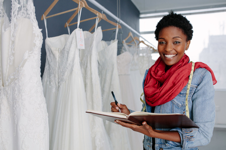 Photo for Portrait of smiling female bridal store owner with a diary. Wedding dress designer working in her boutique. - Royalty Free Image