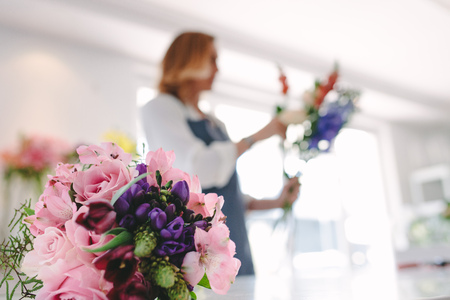 Foto de Colorful flower bouquet on counter with female florist working in background. Focus on fresh flower bouquet at florist shop. - Imagen libre de derechos