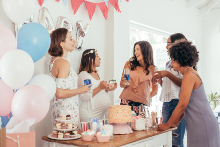 Photo for Pregnant woman celebrating baby shower party with female friends at home. Group of multi-ethnic women at a baby shower. - Royalty Free Image