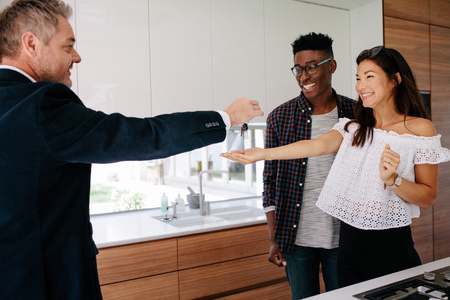 Foto de Real estate agent handing over keys of new home to young couple. Happy new property owners with estate broker. - Imagen libre de derechos