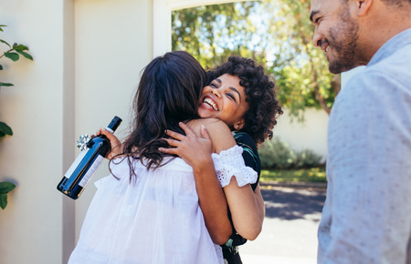 Photo for Woman greeting couple for having a new house. Smiling young woman with wine bottle congratulating her friend. Housewarming party with friends. - Royalty Free Image