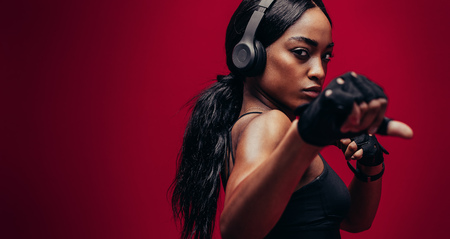 Foto de Strong young woman with headphones practising boxing. African female boxer exercising on red background - Imagen libre de derechos
