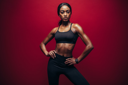 Foto de Young woman wearing black sportswear standing against red background. Healthy african woman with perfect muscular body standing in studio. - Imagen libre de derechos