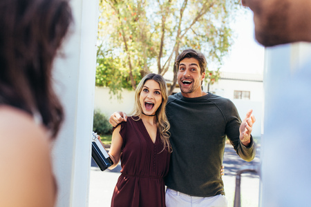 Photo pour Excited couple at entrance door with bottle of wine. Friends being welcomed by couple at the door. Attending friend's housewarming party. - image libre de droit
