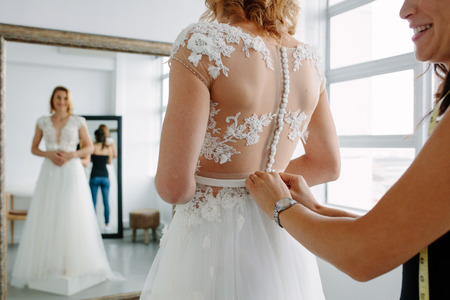 Foto de Bride is standing in front of mirror and fitting dress in atelier with wedding assistant. Woman with dressmaker are making final touch on tailor made gown in bridal clothing shop. - Imagen libre de derechos