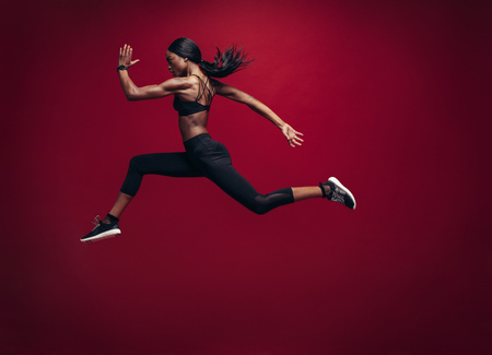 Photo pour Female athlete running and jumping. Side view shot of healthy african woman working out against red background. - image libre de droit