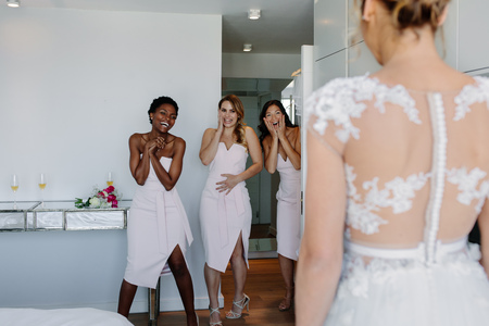 Photo for Surprised bridesmaids looking at beautiful bride in wedding gown in hotel room. Wedding morning bridesmaids looking at bride in wedding dress and smiling. - Royalty Free Image