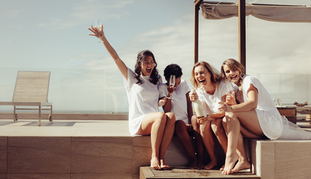 Photo pour Hen party on the rooftop. Bride and bridesmaids having champagne and laughing. Girls are going crazy before wedding. - image libre de droit