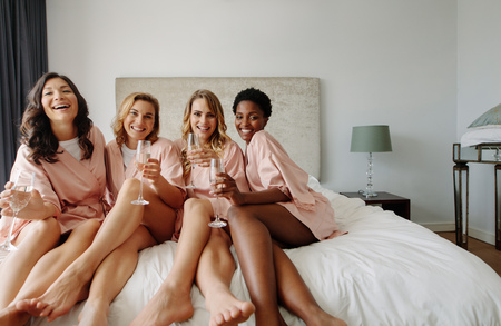 Photo pour Bride and bridesmaids celebrating bachelorette party in bedroom. Happy females friends sitting on bed and having champagne. - image libre de droit