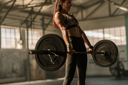 Foto de Determined and strong fitness woman training with heavy weights in fitness club. Female athlete holding heavy weight barbell in gym. - Imagen libre de derechos