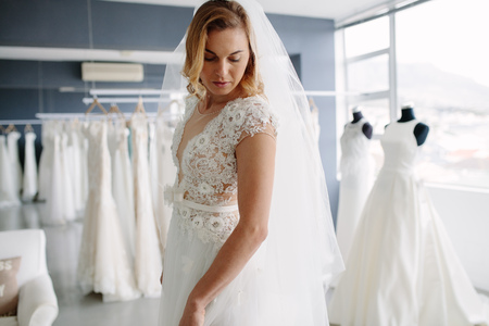 Photo for Beautiful young woman trying on bridal gown in wedding fashion shop. Caucasian female trying her wedding dress at bridal boutique. - Royalty Free Image