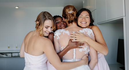 Photo for Cheerful bridesmaids embracing bride in wedding gown in hotel room. Wedding day, happy bridesmaids congratulating the bride and smiling. - Royalty Free Image