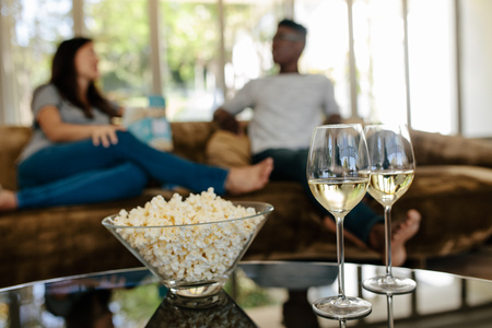 Foto de Bowl of popcorn and wine glasses on table in front with couple sitting and relaxing on couch in background. - Imagen libre de derechos