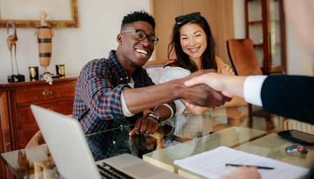 Photo for Happy property owners shaking hands with real estate broker after a deal. Young couple handshaking real estate agent after signing contract. - Royalty Free Image