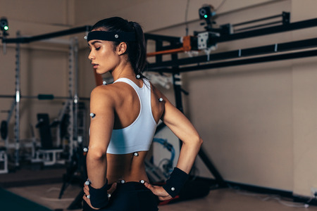 Foto de Sportswoman with motion capture sensors on her body to measure the movement during sports at biomechanical lab. - Imagen libre de derechos