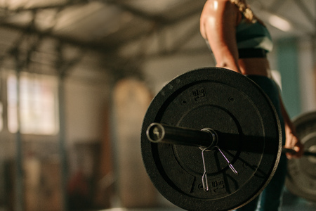 Foto de Woman exercising with heavy weights in health club. Focus on heavy weight barbell in hands of female athlete. - Imagen libre de derechos