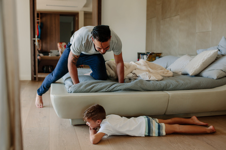 Photo for Father and son playing hide and seek in bedroom. Little boy hiding by the bed with father searching him. Family playing games inside their home. - Royalty Free Image
