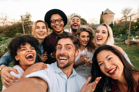Foto de Friends chilling outside taking group selfie and smiling. Laughing young people standing together outdoors and taking selfie. - Imagen libre de derechos