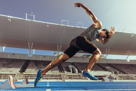 Foto de Athlete starting his sprint on an all-weather running track. Runner using starting block to start his run on running track in a stadium. - Imagen libre de derechos