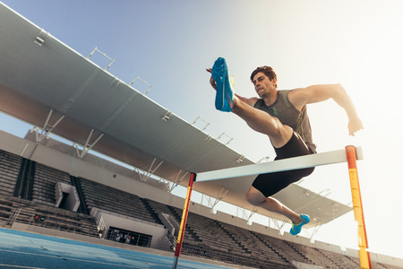 Photo for Close up of a runner jumping over an hurdle during track and field event. Athlete running a hurdle race in a stadium. - Royalty Free Image