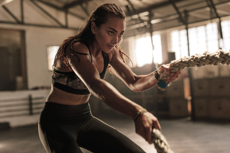 Foto de Fitness woman using battle ropes for exercising. Female working out with battle ropes at cross gym. - Imagen libre de derechos