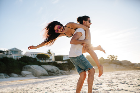 Photo pour Happy young man carrying his woman on the beach. Couple enjoying a day at the beach. - image libre de droit