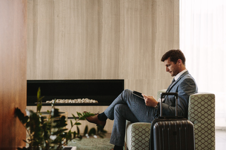 Photo for Side view of business executive reading a magazine while waiting for his flight at airport lounge. Man at airport waiting area reading a magazine. - Royalty Free Image