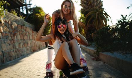 Foto de Women enjoying on their vacation. Happy young female on skateboard with friend pushing. - Imagen libre de derechos