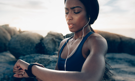 Foto per Close up of young fitness woman looking at her smart watch while taking a break from outdoor workout. Sportswoman checking pulse on fitness smart watch device. - Immagine Royalty Free
