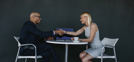 Foto de Two business people shaking hands after a successful meeting. Businessman and woman hand shake at cafe over a deal. - Imagen libre de derechos