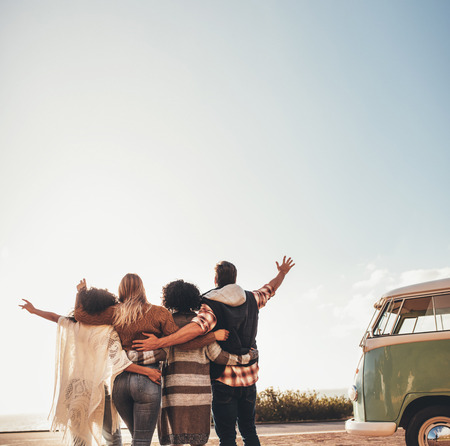 Foto de People enjoying during their road trip. Four friends standing together with their arms raised. - Imagen libre de derechos