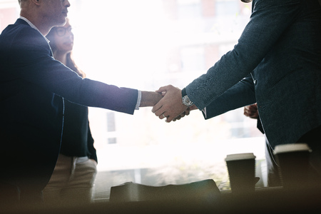 Photo for Business people shaking hands and finishing up a meeting in office. Businessmen handshaking after successful deal. - Royalty Free Image