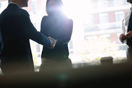 Photo for Businessman and businesswoman shaking hands in board room and finishing up a meeting. Business people hand shake after a successful deal. - Royalty Free Image