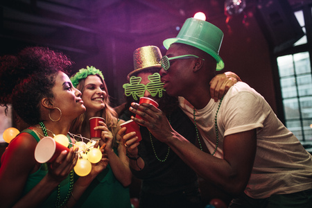 Photo for Multi-ethnic men and women having fun at the bar. Group of friends celebrating St. Patrick's Day at nightclub. - Royalty Free Image