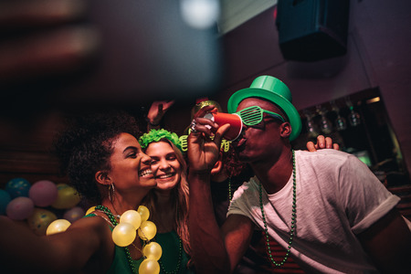 Foto de Man drinking a glass of beer with female friends smiling and taking selfie at bar. Young people celebrating St.Patricks day at night club and taking selfie with phone. - Imagen libre de derechos