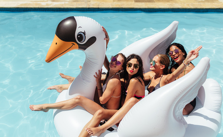 Photo pour Group of friends on vacation sitting together on an inflatable swan in swimming pool. Multi-ethnic women friends enjoying on a inflatable white swan in pool. - image libre de droit