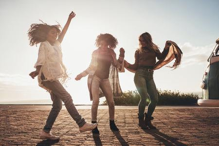 Foto de Female friends dancing on the road. Group of women enjoying a day of road trip. - Imagen libre de derechos
