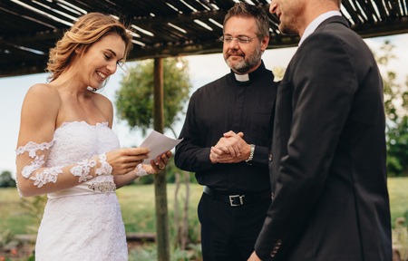 Photo for Woman read vows from paper for her husband at wedding ceremony background. Female partner reading marriage vows in ceremony with priest standing by. - Royalty Free Image