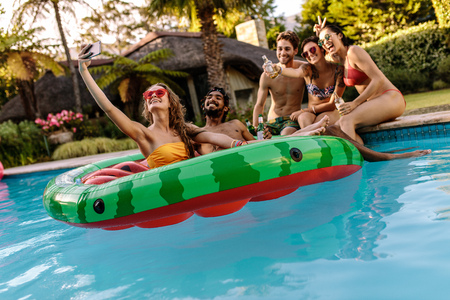 Foto de Multi-racial group of friends having fun in a swimming pool and taking selfie. Cheerful young friends with drinks taking selfie by the pool. - Imagen libre de derechos