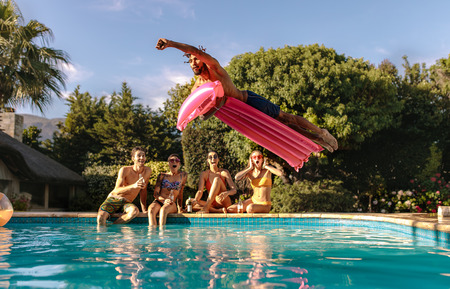 Foto de Man jumping in the swimming pool with inflatable mattress and friends sitting on the edge of the pool. Friends enjoying a summer day at pool side. - Imagen libre de derechos