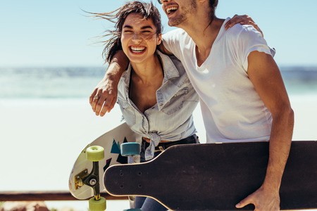 Photo pour Cheerful woman with her boyfriend walking by the beach. Couple with skateboards having fun at the beach. - image libre de droit
