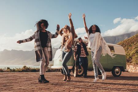 Foto de Group of friends dancing on roadtrip. Woman dancing with man standing by the van outdoors. - Imagen libre de derechos