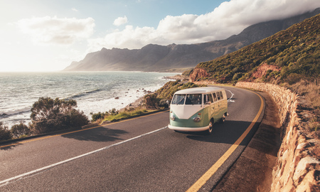 Foto de Mini van on coastal road. Group of friends traveling by a van on highway along the sea. - Imagen libre de derechos