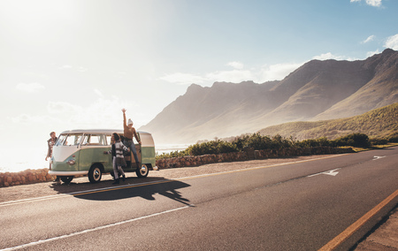 Foto de Friends on road trip on a sunny day. Group of man and women hangout by the road with old minivan. - Imagen libre de derechos