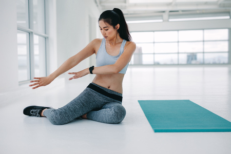Photo for Fitness woman sitting on floor by yoga mat and rehearsing the poses. Female practising yoga moves before the workout session at fitness studio. - Royalty Free Image