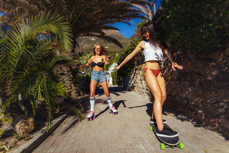 Photo pour Smiling female friends skating during their summer vacation. Women in bikini doing skateboarding on a small path. - image libre de droit