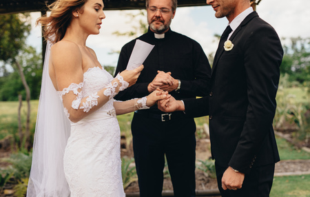 Photo pour Bride holding a paper and reading wedding vows, with minister standing in the background. Couple exchanging vows on wedding ceremony. - image libre de droit
