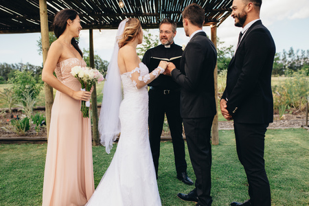 Photo pour Bride and groom standing in front of priest witness by bridesmaids and best man. Outdoor wedding ceremony of beautiful couple. - image libre de droit