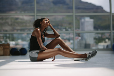 Foto de Tired and exhausted woman resting after intense training session at fitness club. African female taking break from exercise routines at gym. - Imagen libre de derechos
