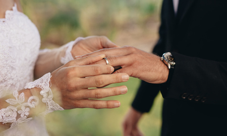 Photo pour Closeup of bride putting a wedding ring onto the groom's finger. Couple exchanging wedding rings. - image libre de droit
